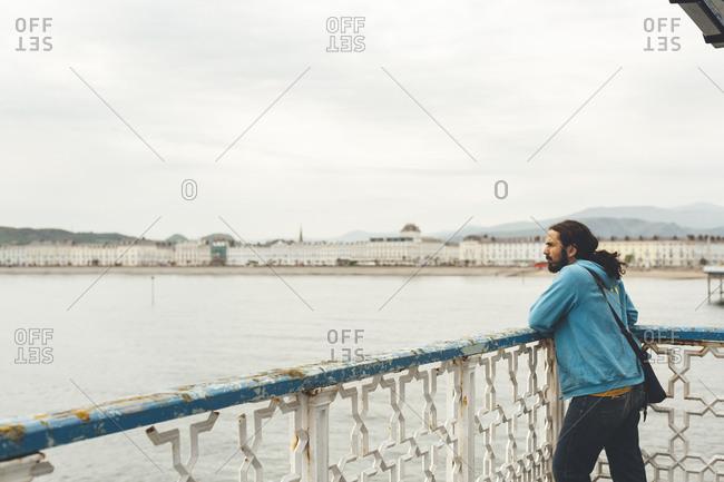 Man looking at Llandudno city from (No Suggestions) Pier, North Wales, UK