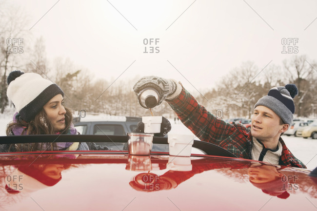 Friend looking at man pouring coffee in cup over car hood