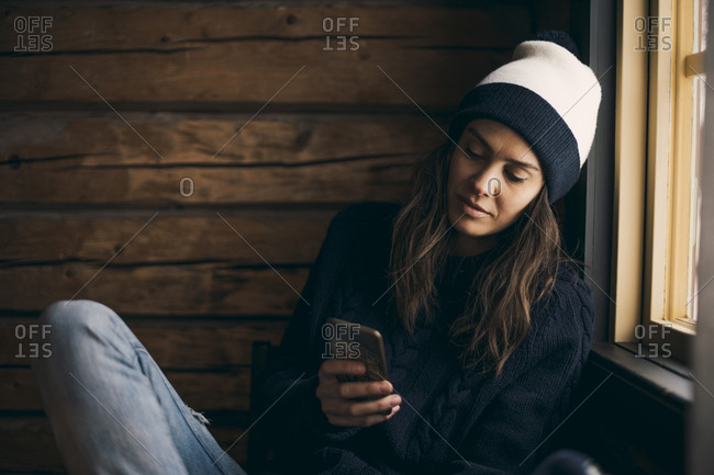 Woman using mobile phone while sitting in log cabin