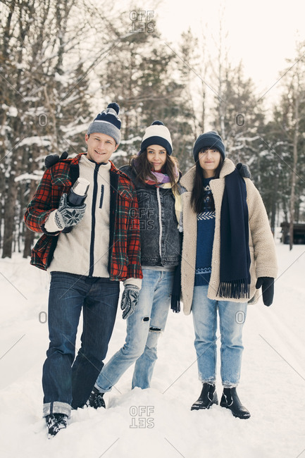 Full length portrait of smiling friends standing against trees on snow covered field