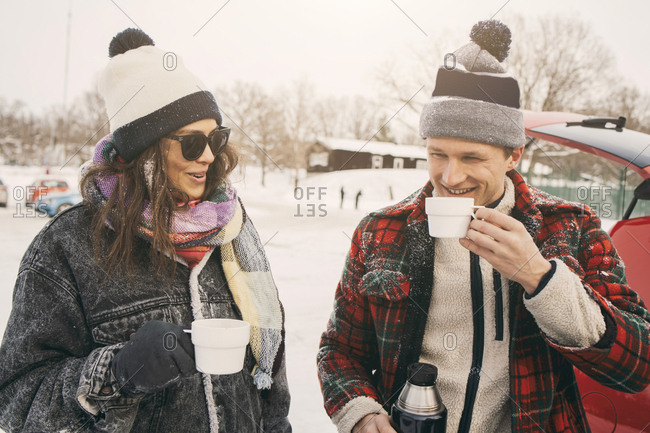 Smiling friends talking while having coffee at snowy park