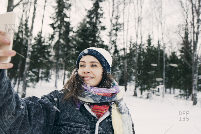 Smiling woman taking selfie through mobile phone while standing against trees on snowy field