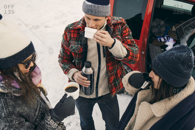 High angle view of friends having coffee while talking by car on snow