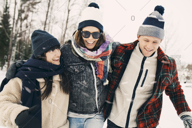 Cheerful male and female friends enjoying at park during winter
