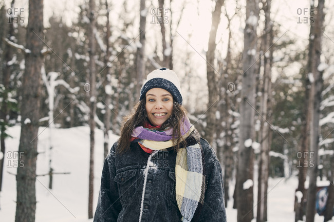 Portrait of smiling mid adult woman standing against bare trees during winter