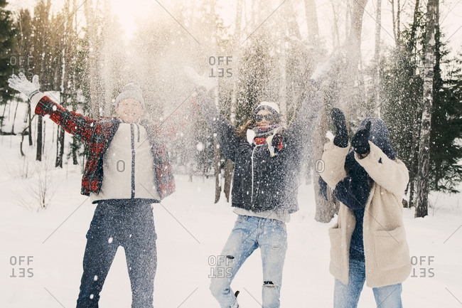 Playful friends throwing snow while standing on field at park