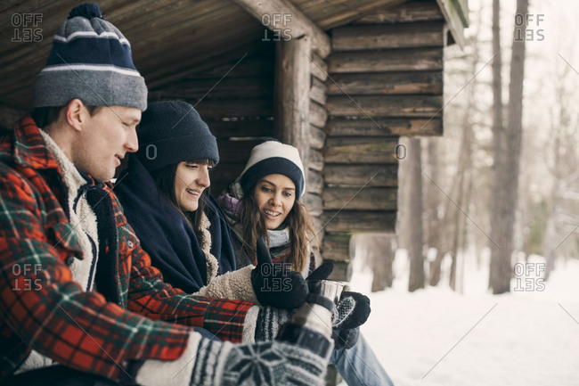 Man giving drink to female friends while sitting at log cabin during winter