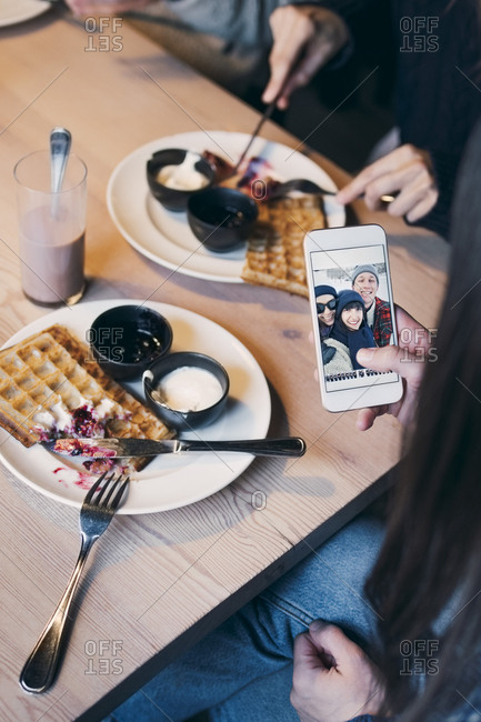 Cropped image of woman looking at photograph on smart phone screen while having breakfast with friends
