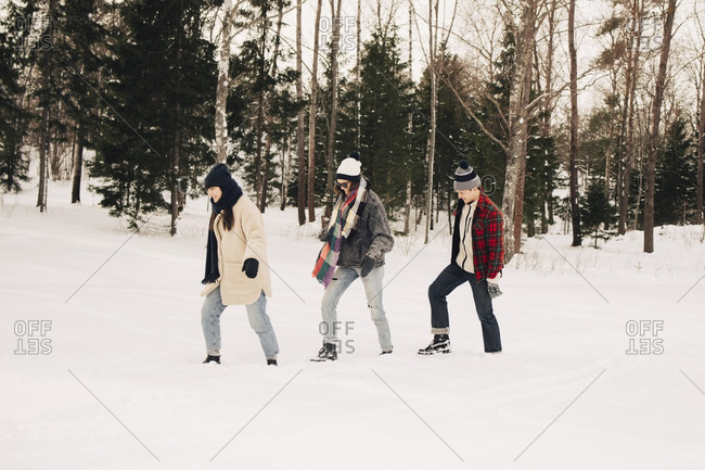 Full length of friends walking on snow by trees at park