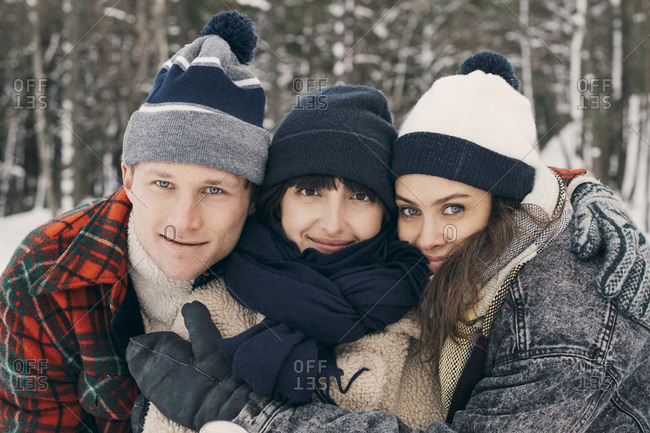 Portrait of friends embracing at park during winter