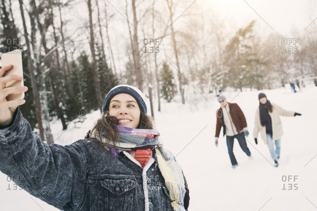 Smiling woman taking selfie while friends walking in background