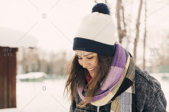 Smiling mid adult woman looking away at snow covered park