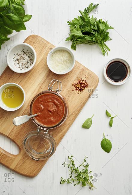 Jar of freshly made marinara sauce surrounded by ingredients