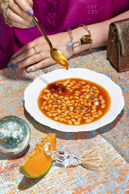 Person eating soup with beans and diamond rings