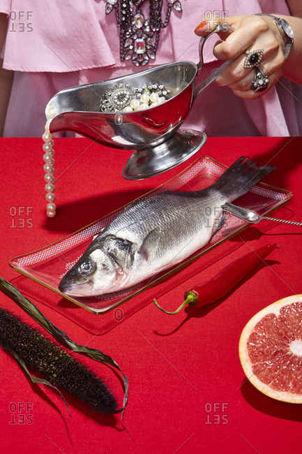 Person pouring a string of pearls from a gravy boat over a whole fish