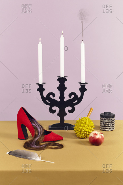Candelabra on table with shoe, feather, fruit, and other objects