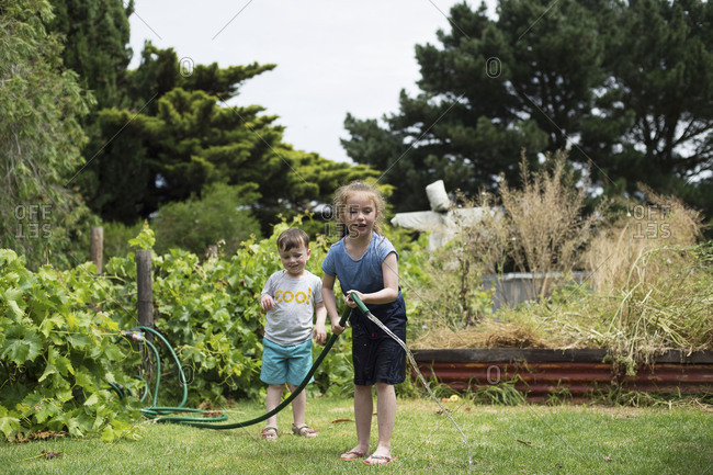 Kids water the lawn with garden hose on a hot day