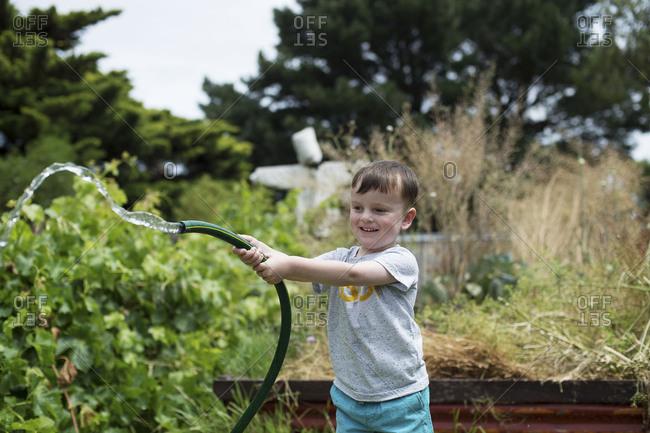 Boy plays with garden hose in the summer heat