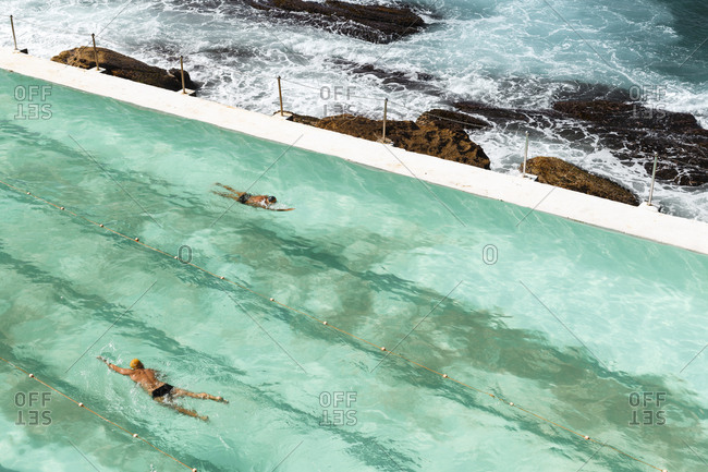 Two people swimming in a pool close to the sea