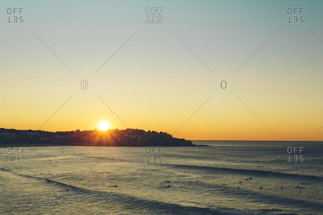 Sunrise over the ocean on a beach with surfers