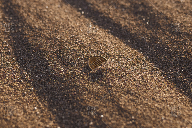 Coin buried in the sand
