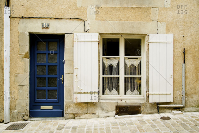 Poitiers, France - August 7, 2018: Old blue door, white window with wooden shutters and lace curtains