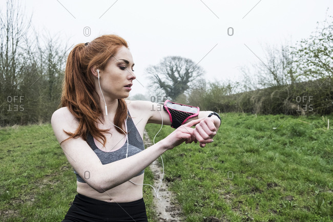 Young woman with long red hair wearing sportswear, exercising outdoors, checking her watch