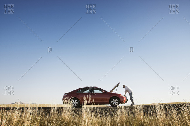 A man looking into the engine compartment of his car parked along a highway in eastern Washington State, USA