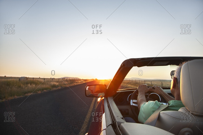 A senior Hispanic man at the wheel of his convertible sports car at sunset in eastern Washington State, USA