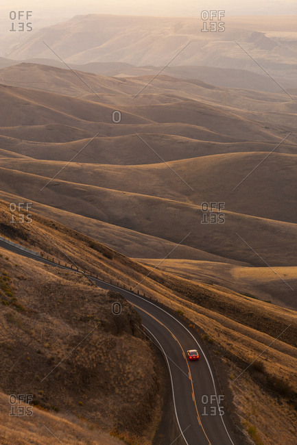 A view looking down of a car moving on a highway at sunrise near Lewiston, Idaho USA