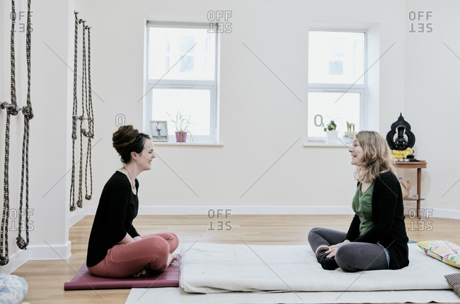 Two women sitting crossed legged facing each other in an exercise studio