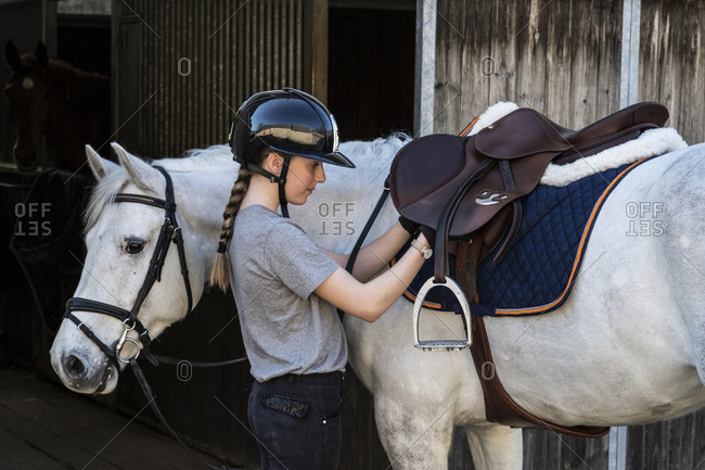 Teenage girl horse rider with a grey horse outside a stable, adjusting the girth and saddle