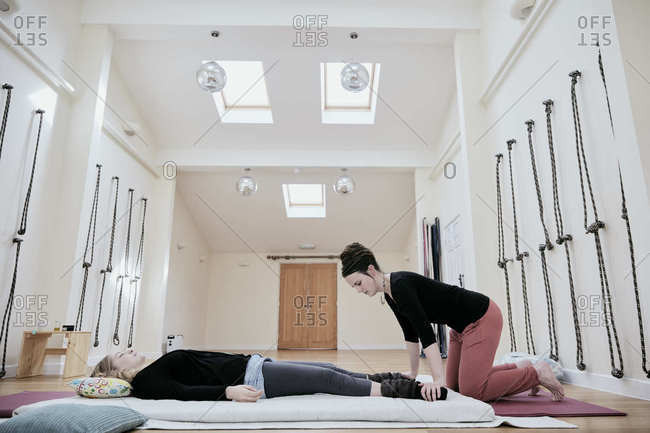 Woman lying down fully clothed having a Thai massage in a light filled exercise studio