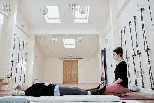 Woman lying down on her back fully clothed in preparation for a Thai massage