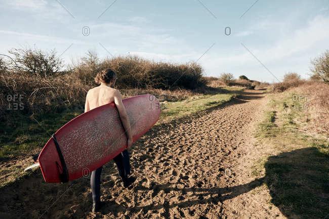 Man holding surf board walking along sandy path towards beach