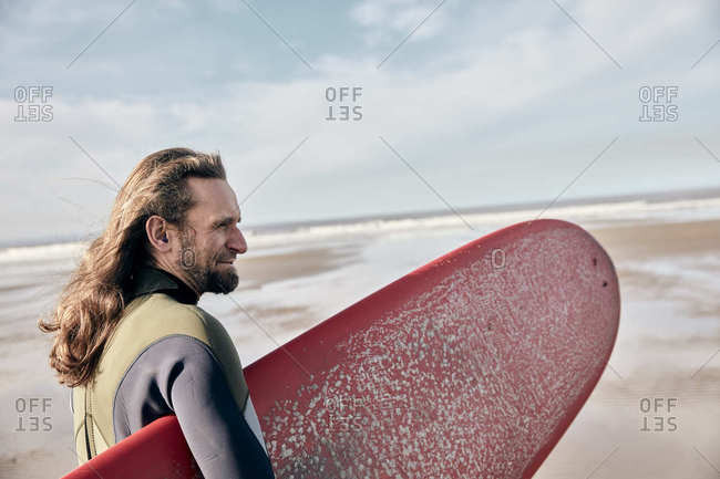 Man holding a full size surf board standing on beach looking out to sea