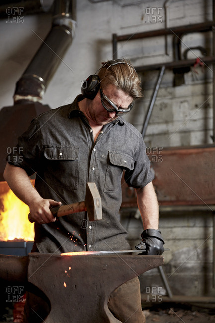 An artisan metal worker in ear protectors using a hammer to shape a red hot piece of metal on an anvil