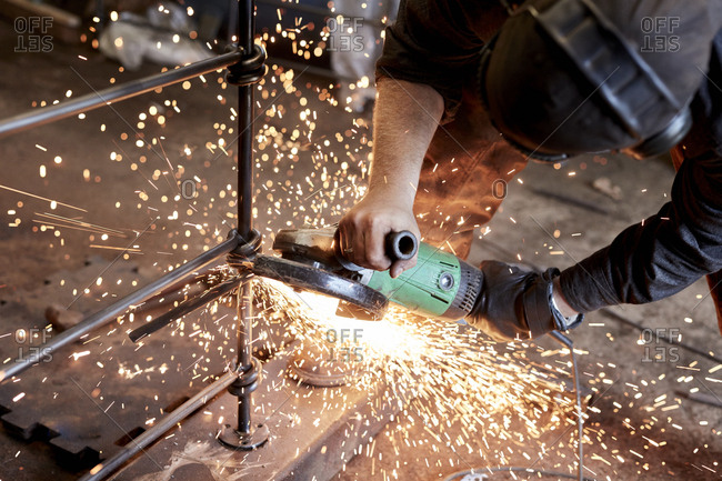 An artisan metalworker at work holding an angle grinder, working on a metal fence