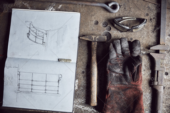 Still life of artisan metalworker's tools, sketches in a notebook and a blackened thick protective glove