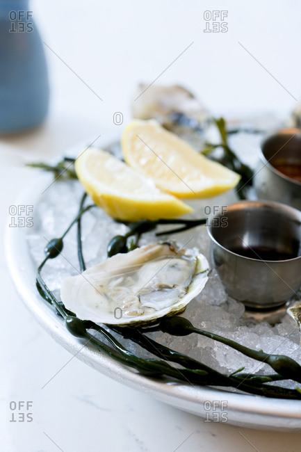 Platter of oysters on ice with lemons and sauces