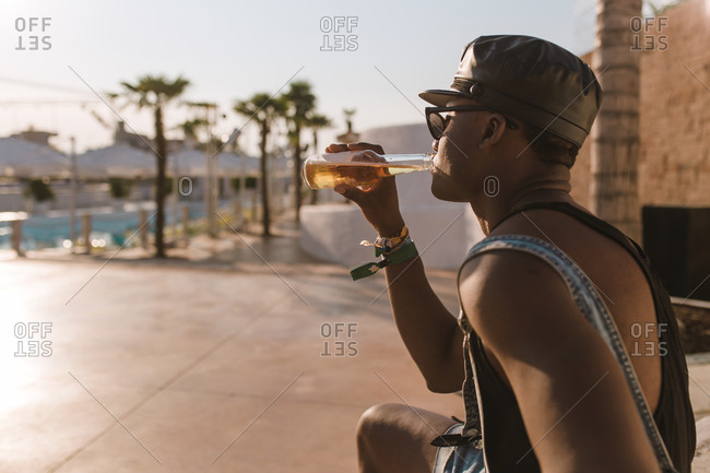 African american boy drinking a beer on a sunset palms background