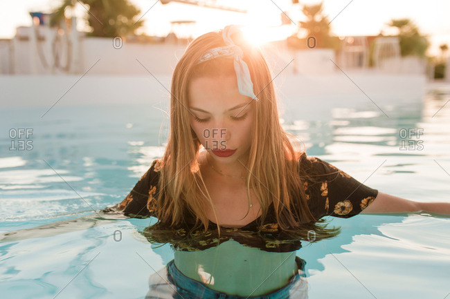Young blond vintage girl with denim short pants and bandana posing and moving by the water on a pool in a sunset of a sunny day of summer