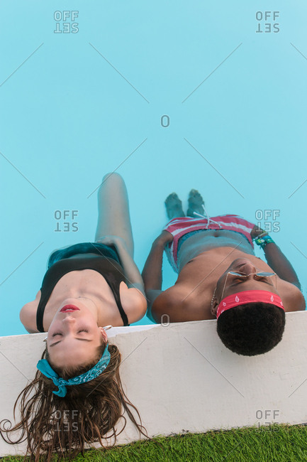 Couple of mixed race friends relaxing on the edge of a swimming pool in an afternoon of a summer day