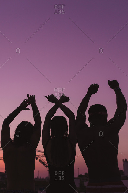 Three friends putting up their hands in a purple sunset of summer