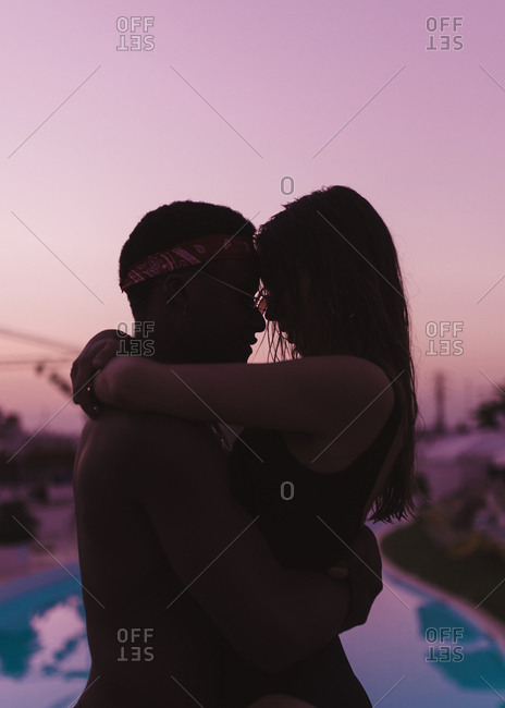 Side view of silhouette of mixed race couple embraced on the swimming pool in a purple sunset of summer
