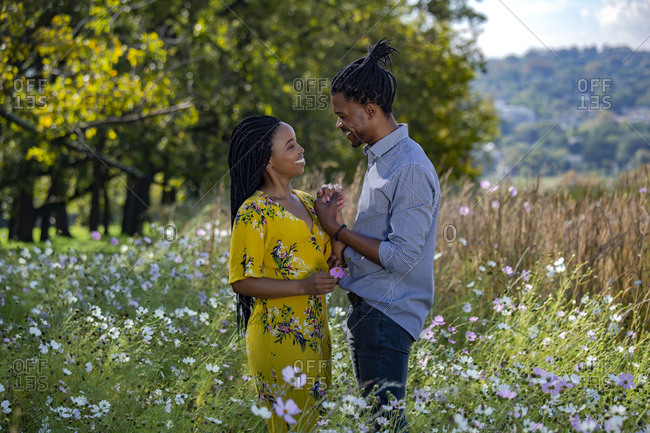 Couple holding hands in a field and laughing