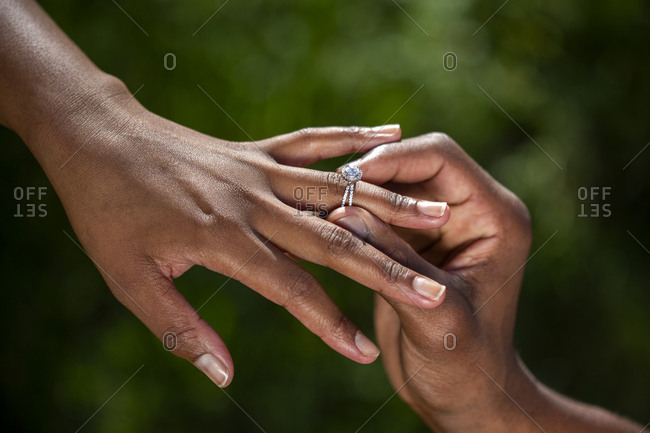 Engagement ring being put on African woman's finger