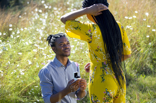 African man proposing to African woman in field