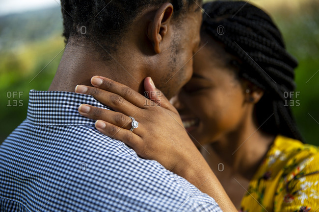 African woman placing hand with engagement ring on African mans neck