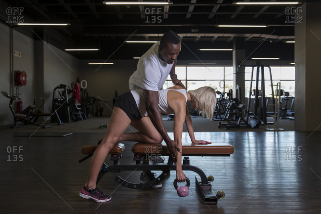 Caucasian woman lifting a kettlebell with her personal trainer assistance
